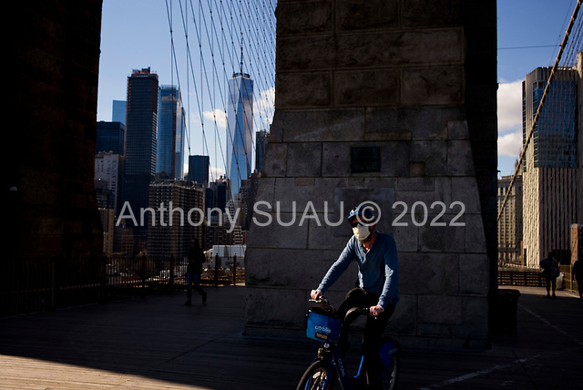 """Brooklyn, New York<br /> April 4, 2020<br /> <br /> Brooklyn Bridge into Manhattan.<br /> <br /> The coronavirus has transformed urban architectural spaces with fear of proximity. Not entirely void of humanity, social distancing, within expansive city environments has created a landscape of aggrandizing physical structures and expanding spaces while diminishing the scale of humans. Face masks enhance the anonymity of """"the person"""", reducing them to a figure or an uninterrupted shadow falling on a surface."""