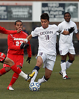 University of Connecticut midfielder Carlos Alvarez (10) dribbles under pressure..NCAA Tournament. With a goal in the second overtime, University of Connecticut (white) defeated University of New Mexico (red), 2-1, at Morrone Stadium at University of Connecticut on November 25, 2012.
