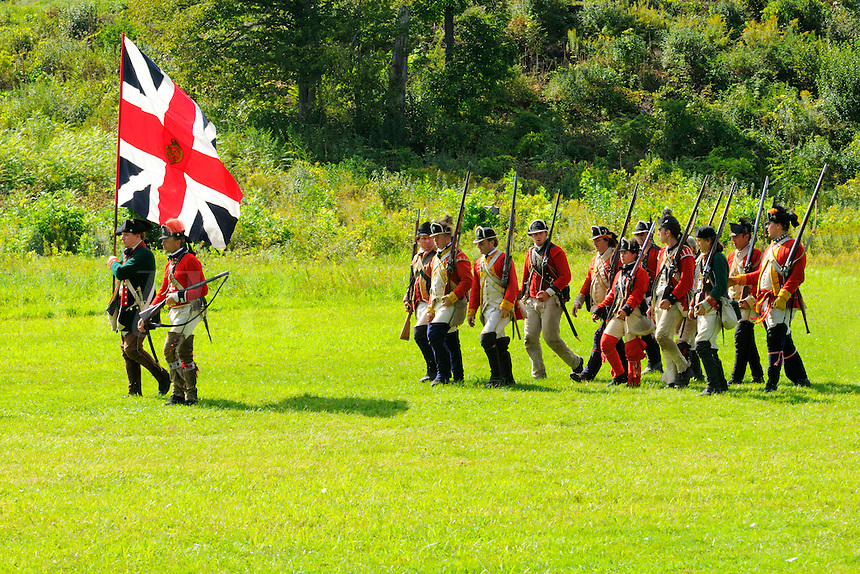 Regimental colors of Loyalist Butler's Rangers, lead green coated Rangers and British redcoats off the battlefield during a Revolutionary War re-enactment at Fort Ticonderoga, New York, USA.