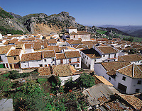 The tiled roofs of the town and church of Grazelema under an enclosing rocky ridge in the Serrania de Ronda, southern Spai