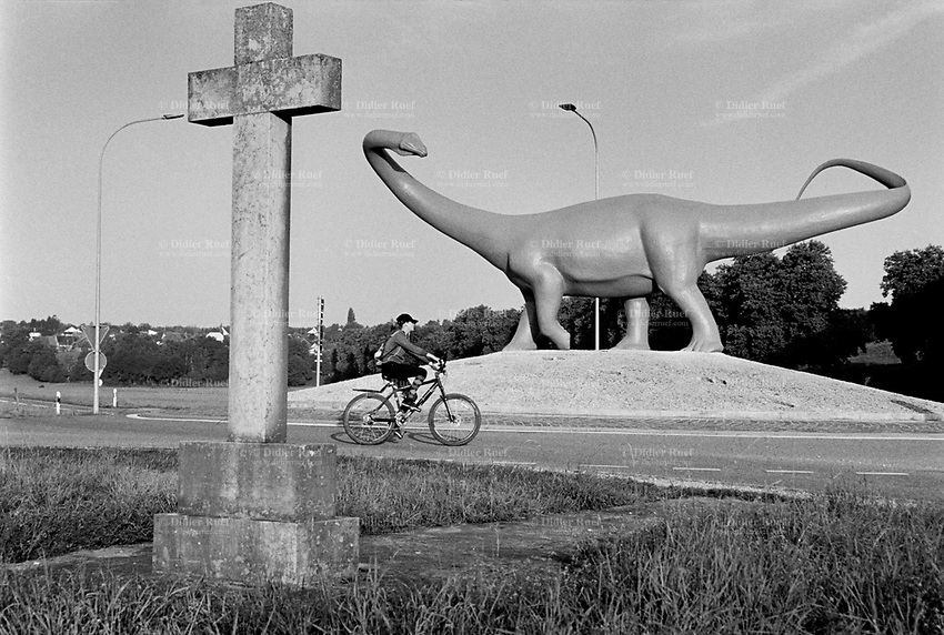 Switzerland. Canton Jura. Porrentruy. A life-size prehistoric diplodocus, created by the sculptor Hervé Bénard, on a roundabout at the town's west exit. A teenage woman rides her bicycle in the early morning. An antique catholic stone cross stands on the side of the roundabout. 15.08.2017 © 2017 Didier Ruef