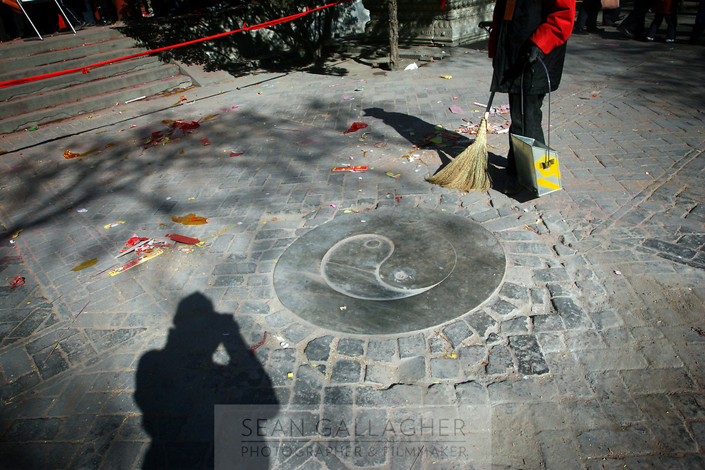 CHINA. A worker sweeping during Chinese New Year in Baiyun Temple in Beijing.  Chinese New Year, or Spring Festival, is the most important festival and holiday in the Chinese calendar In mainland China, many people use this holiday to visit family and friends and also visit local temples to offer prayers to their ancestors. The roots of Chinese New Year lie in combined influences from Buddhism, Taoism, Confucianism, and folk religions.  2008