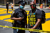 "NEW YORK, NEW YORK - June 14: A policeman poses with a man in the making of the ""Black Lives Matter"" mural on Fulton St in the Bedford - Stuyvesant neighborhood on June 14, 2020 in Brooklyn, NY. Protesters continue Nationwide after the death of George Floyd. (Photo by Pablo Monsalve/VIEWpress via Getty Images)"