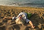 Older woman lying on the beach, enjoying the warm sand