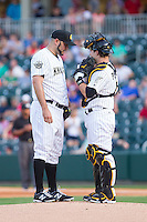 Charlotte Knights catcher Josh Phegley (4) has a chat on the mound with starting pitcher Felipe Paulino (39) during the game against the Lehigh Valley IronPigs at BB&T Ballpark on May 8, 2014 in Charlotte, North Carolina.  The IronPigs defeated the Knights 8-6.  (Brian Westerholt/Four Seam Images)