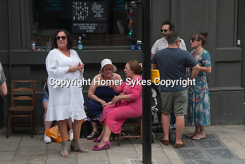 Italian community, annual procession starting from the Italian Church Saint St Peters London. 2018. Group of Italians catching up outside a pub.