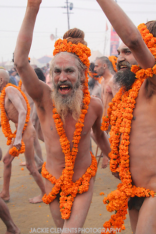 A pair of joyous Naga sadhus with their dreadlocks twisted up onto their heads walk in the parade to bath in the holy waters.