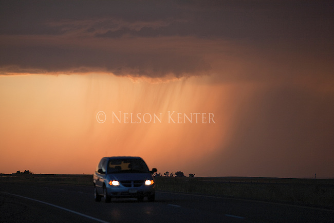 Freeway traffic in eastern Montana with storm clouds and the setting sun