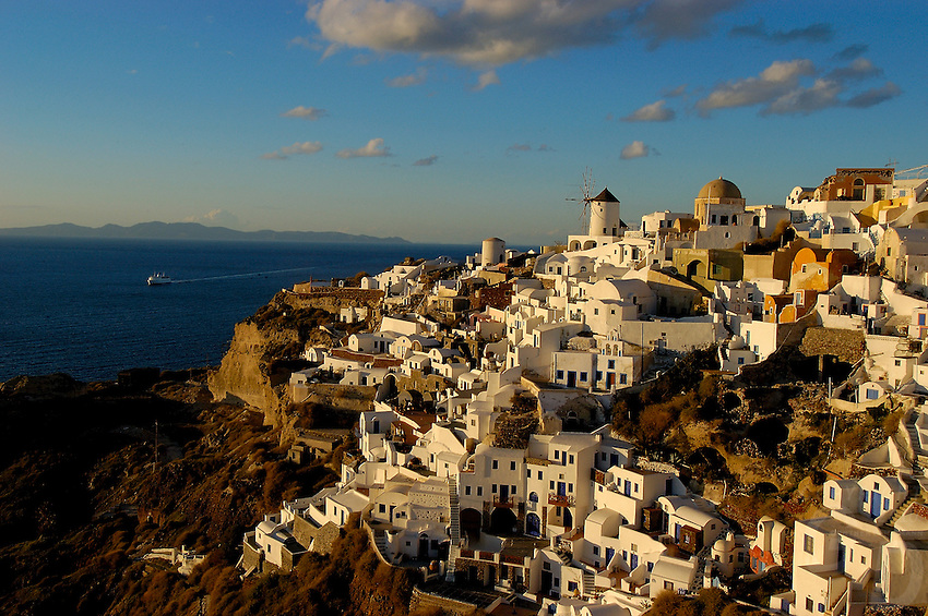 Late afternoon overlooking one of the villages at Santorini, and a Ferry in the background,the unusual buildings and a windmill set the scene,Santorini, Greece