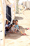 DOMIZ, IRAQ: Young girls sit outside a tent in the Domiz refugee camp...Over 7,000 Syrian Kurds have fled the violence in Syria and are living in the Domiz refugee camp in the semi-autonomous region of Iraqi Kurdistan...Photo by Ari Jalal/Metrography