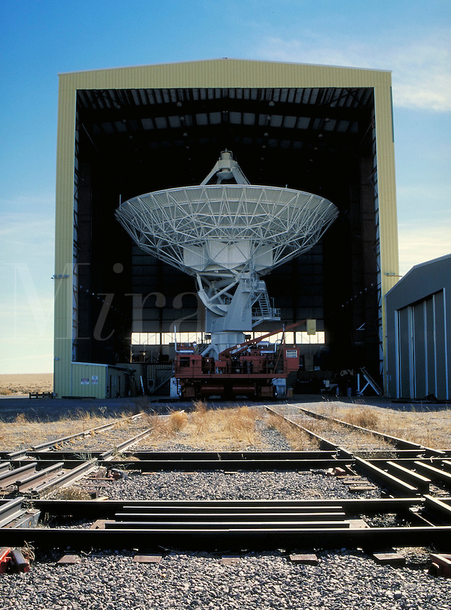 Very Large Array (VLA).   Antenna Assembly Building with antenna inside. Red vehicle in front of antenna is a transporter vehicle used for moving the antenna. New Mexico, Plains of San Agustin.