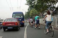 Cars and bicycles compete for space on a road during a traffic jam in Beijing, China.