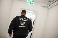 """Am Freitag den 10. Juli 2015 wurde der erste von zwei Containerunterkuenften fuer Fluechtlinge aus dem Buergerkrieg in Syrien im Berliner Bezirk Marzahn-Hellersdorf bei einem """"Tag der offenen Tuer"""" der Presse vorgefuehrt.<br /> Gegen die Errichtung der zwei Containerunterkuenfte haben mehrere Monate Anwohner sowie Nazis und Hooligans aus Berlin und Brandenburg protestiert. Zum Schutz der Containerunterkuenfte vor rassistischen Protesten waren Mitarbeiter einer Securityfirma und eine Hunderschaft der Polizei vor Ort.<br /> Im Bild:  Ein Polizeibeamter in dem fertiggestellten Containerhaus.<br /> 10.7.2015, Berlin<br /> Copyright: Christian-Ditsch.de<br /> [Inhaltsveraendernde Manipulation des Fotos nur nach ausdruecklicher Genehmigung des Fotografen. Vereinbarungen ueber Abtretung von Persoenlichkeitsrechten/Model Release der abgebildeten Person/Personen liegen nicht vor. NO MODEL RELEASE! Nur fuer Redaktionelle Zwecke. Don't publish without copyright Christian-Ditsch.de, Veroeffentlichung nur mit Fotografennennung, sowie gegen Honorar, MwSt. und Beleg. Konto: I N G - D i B a, IBAN DE58500105175400192269, BIC INGDDEFFXXX, Kontakt: post@christian-ditsch.de<br /> Bei der Bearbeitung der Dateiinformationen darf die Urheberkennzeichnung in den EXIF- und  IPTC-Daten nicht entfernt werden, diese sind in digitalen Medien nach §95c UrhG rechtlich geschuetzt. Der Urhebervermerk wird gemaess §13 UrhG verlangt.]"""