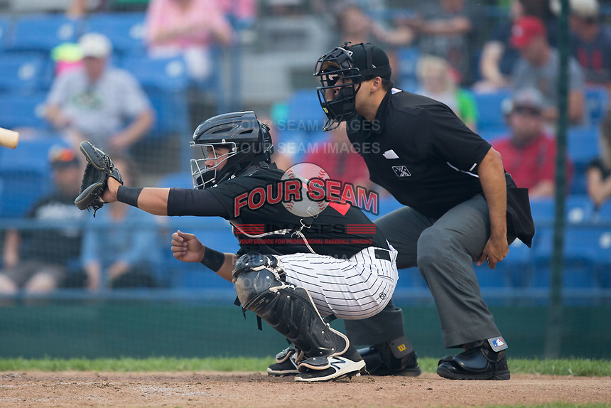 Great Falls Voyagers catcher Carlos Perez (20) sets a target as home plate umpire Edgar Huerta-Morales looks on during the game against the Helena Brewers at Centene Stadium on August 18, 2017 in Helena, Montana.  The Voyagers defeated the Brewers 10-7.  (Brian Westerholt/Four Seam Images)