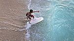 A young boy attempts his skill at skim boarding off the shores of Waikiki Beach, Hawaii.