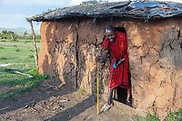 Tanzania.  Maasai Man Exiting His House in Village of Ololosokwan, Northern Serengeti.