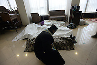 A Orthodox priest blesses dead bodies in the Makeshift clinic and morgue inside the hotel Ukraine lobby. Death and injury toll raise every hour on the hour in Maidan square since the violent repression started. Kiev, Ukraine