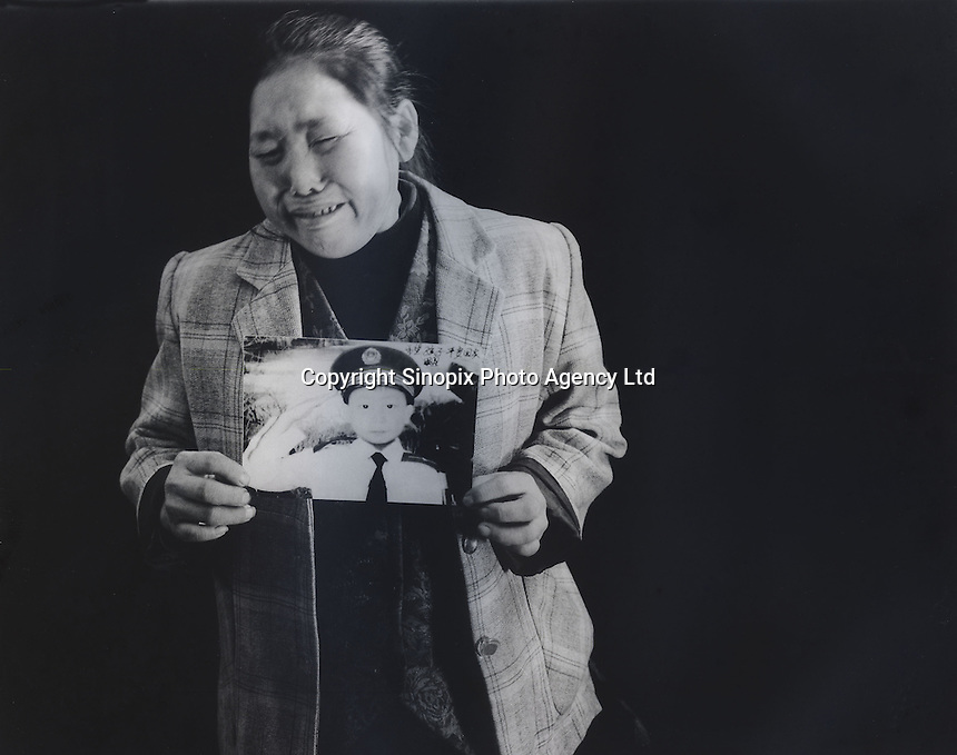 """Mrs Xiang, 40, holds a picture of her son Ren Pan, who was 4 and half years old when he was stolen 9th September 2003. The message reads """"Hope my son can come back home safe.""""..PHOTO BY SINOPIX"""