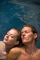 Young couple floating in water, eyes shut, elevated view