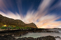 A view of tidal pools backed by the Ko'olau mountains under a starry night sky streaked with clouds, Makapu'u Beach, Waimanalo, O'ahu.