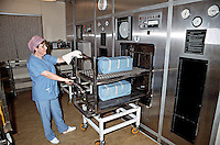 Staff filling the autoclave sterilizing unit in a hospital. The autoclave is used to sterilize surgical instruments and surgical drapes. This image may only be used to portray the subject in a positive manner..©shoutpictures.com..john@shoutpictures.com