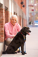Outdoor portrait of man with dog in Tribeca.