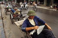 Asie/Vietnam/Haiphong: conducteur de cylo-pousse lisant en attendant leurs clients