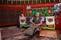 Mongolia, Bayan-Ulgii, Ulgii, Altai Mountains. Family in their yurt near Tsambagarav Mountain. Kazakh woman sewing felt.