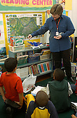 MR / Schenectady, NY.Yates Arts in Education Magnet School, Grade 2.Arts-Themed Urban Elementary School.Teacher does demonstration using weight balance for class science lesson on weight and measurement..MR: Car19.© Ellen B. Senisi