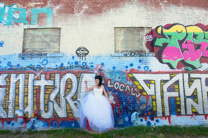 Bride standing against a wall of graffiti