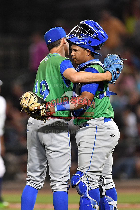 Pitcher Garrett Davila (19) and catcher Meibrys Viloria (4) of the Lexington Legends embrace after the final pitch in a game against the Columbia Fireflies on Saturday, April 22, 2017, at Spirit Communications Park in Columbia, South Carolina. Lexington won, 4-0. (Tom Priddy/Four Seam Images)