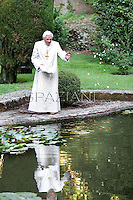 Pope Benedict XVI feeds red fish in a pond of the papal summer retreat of Castel Gandolfo, on July 23, 2010 on the hills in the outskirts of Rome. SPAZIANI/ POOL/ OSSERVATORE ROMANO