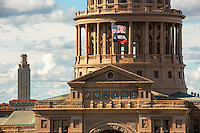 In this image, The Texas Capitol Dome highlighting the the Six mosaic seals of Texas and an American and Texas flag flying above with the University of Texas Tower behind. The six seal mosaics represent the six countries that had soverignty over what became the state of Texas.  Those countries are: Spain (1519-1821), France (1685-1690), Mexico (1821-1836), the Republic of Texas (1836-1845), the Confederate States of America (1861-1865), and the United States of America (1845-1861; 1865-present)  - Stock image