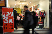 A clothes store offers 30% off in a sale in Hong Kong's Central district. Hong Kong's slumping economy will shrink further in the first half of 2009..