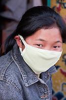 Bodhnath, Nepal.   Young Nepali Woman with Beeathing Mask at the Buddhist Stupa of Bodhnath.