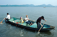China. Province of Zhejiang. Hangzhou. On a sunny sunday afternoon,  chinese tourists ride a rowing boat on West Lake. © 2004 Didier Ruef