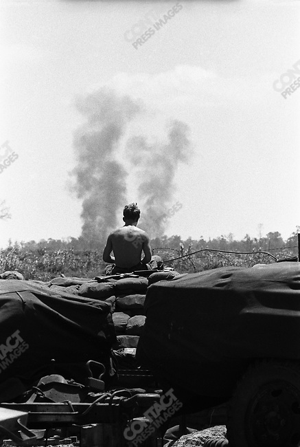American troop sitting on sand bags watching air strikes in the distance, near Quang Tri, South Vietnam, February 1972