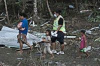 A young woman and her chidren are helped by a woman police officer as they walk through the debris near their home at Lalomanu. More than 170 people died when a tsunami triggered by an 8.3 magnitude earthquake hit Samoa and neighbouring Pacific islands on 29/09/2009. Samoa (formerly known as Western Samoa)..