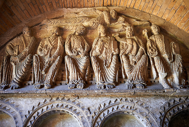 """Early Anglo Saxon sulptures of Christ and the  Apostles now part of the south porch of Malmesbury Abbey, Wiltshire, England. The apostles, apart from Peter who holds a crude key, have no distinguishing feature to allow identification. Some are holding books, none have halos and some hold their heads at awkward angles. These three styles are typical of Anglo Saxon art. The two panels are 10 ft long and 4ft 6"""" high are date from the original Ango Saxon church of 705. They were probablbly built into the proch during the Norman rebuilding. The style of these sculptures is of the Roman Byzantine style and were probably sculpted by masions from Gaul.  Malmesbury Abbey, Wiltshire, England"""