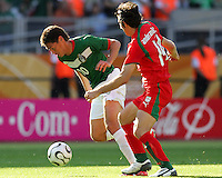 Guillermo Franco of Mexico stumbles forward in front of Andranik Teymourian of Iran. Mexico defeated Iran 3-1 during a World Cup Group D match at Franken-Stadion, Nuremberg, Germany on Sunday June 11, 2006.