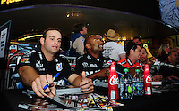 Oct. 27, 2011; Las Vegas, NV, USA: NHRA funny car driver Matt Hagan (left) and top fuel dragster driver Antron Brown sign autographs during the fanfest at Fremont Street. Mandatory Credit: Mark J. Rebilas-US PRESSWIRE