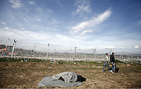 Pictured: Refugees walk by the fenced off Greek FYRO Macedonian border Thursday 25 February 2016<br /> Re: Refugees have been left stranded in temporary camps after Greek FYRO Macedonian borders were closed in Idomeni, northern Greece.