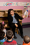 Education Preschool 3-4 year olds circle time female teacher reading picture book to group of children vertical