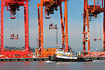 A tugboat sails past cranes at the Port of Seattle