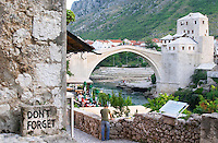 View along the river of the old reconstructed bridge. The busy old market bazaar street Kujundziluk with lots of tourist craft and art shops and street merchants. A sign saying 'don't forget'. A lone man standing on the street. Historic town of Mostar. Federation Bosne i Hercegovine. Bosnia Herzegovina, Europe.