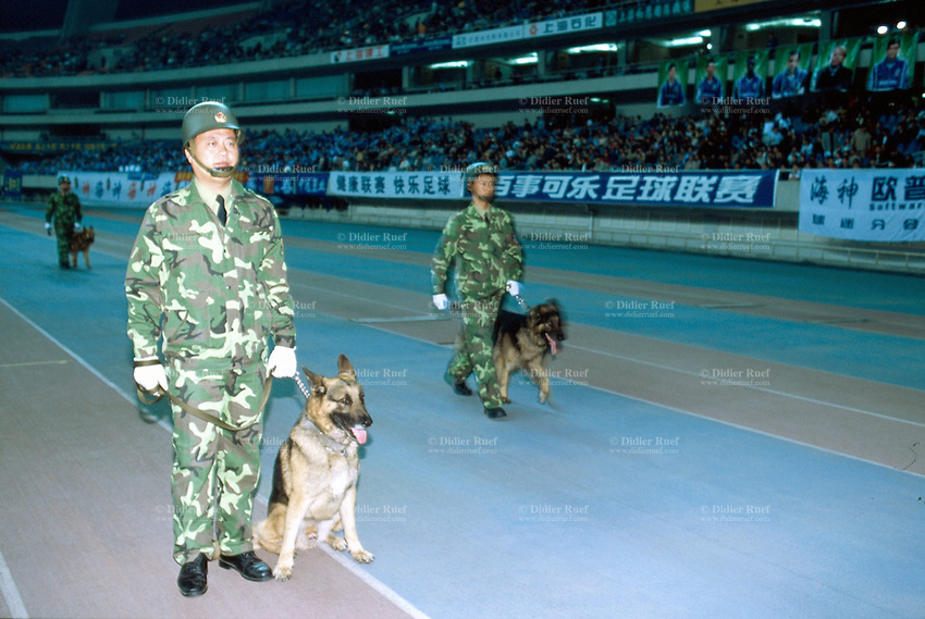 China. Shanghai. Shanghai stadium. Policemen dressed in camouflage clothes are keeping dogs on leads for safety measures on the ground before the start of a football game. © 2002 Didier Ruef