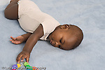 5 month old baby boy African American rolling over to reach and grasp toy horizontal