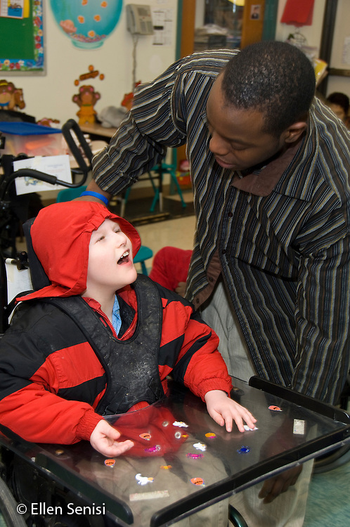 MR / Albany, NY.Langan School at Center for Disability Services .Ungraded private school which serves individuals with multiple disabilities.Teaching assistant (African-American) and student say goodbye as he gets student ready to go home. Boy: 9, cerebral palsy, non verbal with expressive and receptive language delays.MR: Law4, Wes2.© Ellen B. Senisi