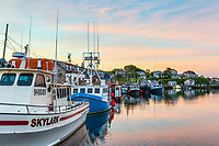 Commercial fishing boats docked in Menemsha Basin under a colorful pre-sunrise sky, in the fishing village of Menemsha in Chilmark, Massachusetts on Martha's Vineyard.