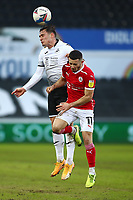 19th December 2020; Liberty Stadium, Swansea, Glamorgan, Wales; English Football League Championship Football, Swansea City versus Barnsley; Connor Roberts of Swansea City heads the ball whilst pressured by Conor Chaplin of Barnsley